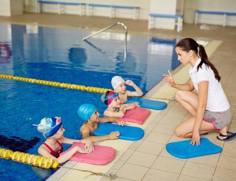 Photographie d'enfants et d'une encadrante à la piscine illustrant le BPJEPS