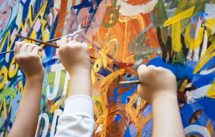 Photographie de la réalisation d'une peinture par des enfants
